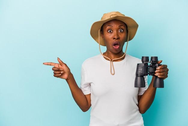 側面を指している青い背景に分離された双眼鏡を保持している若いアフリカ系アメリカ人女性