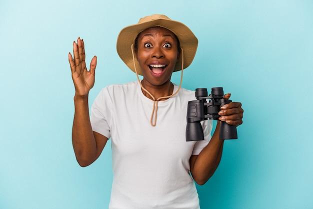 青い背景に分離された双眼鏡を持っている若いアフリカ系アメリカ人の女性は、嬉しい驚きを受け取り、興奮し、手を上げます。