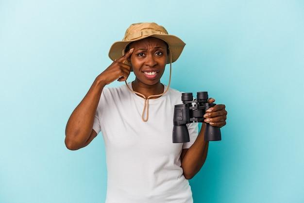 人差し指で失望のジェスチャーを示す青い背景に分離された双眼鏡を保持している若いアフリカ系アメリカ人の女性。