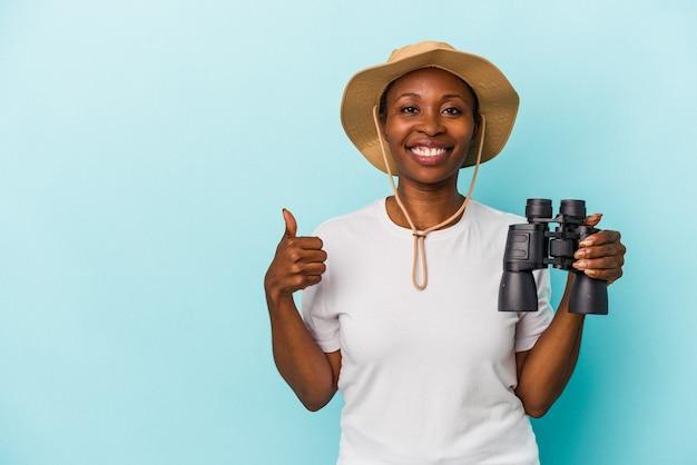 笑顔と親指を上げて青い背景に分離された双眼鏡を保持している若いアフリカ系アメリカ人女性