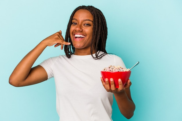 Young african american woman holding a bowl of cereales isolated on blue background  showing a mobile phone call gesture with fingers.