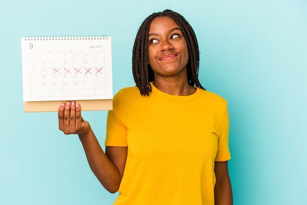 Young african american woman holding a calendar isolated on blue background  dreaming of achieving goals and purposes