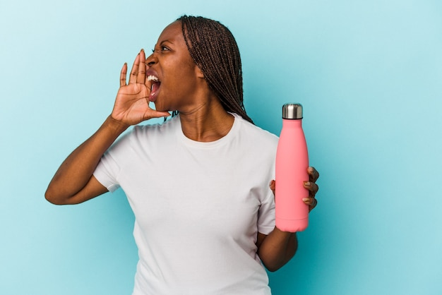 Young african american woman holding canteen isolated on blue background shouting and holding palm near opened mouth.