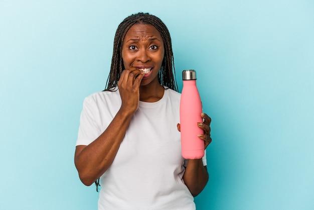 神経質で非常に不安な、青い背景の爪を噛んで孤立した食堂を保持している若いアフリカ系アメリカ人の女性。