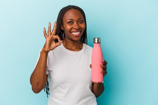 青の背景に分離された食堂を保持している若いアフリカ系アメリカ人女性は、陽気で自信を持って大丈夫なジェスチャーを示しています。