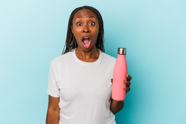 非常に怒って攻撃的に叫んで青い背景で隔離の食堂を保持している若いアフリカ系アメリカ人の女性。