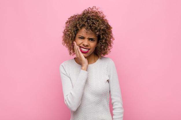 Молодая афро-американская женщина, держащая щеку и страдающая от болезненной зубной боли, чувствует себя больной, несчастной и несчастной, ищет дантиста у розовой стены