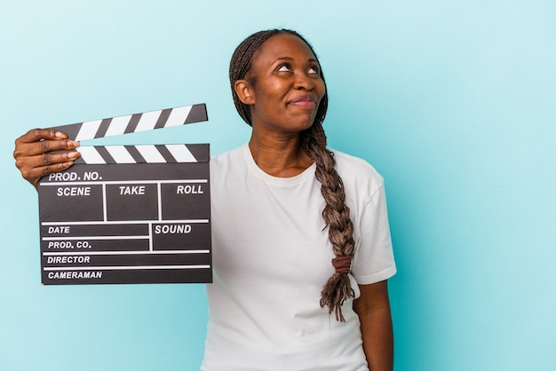 Young african american woman holding clapperboard isolated on blue background dreaming of achieving goals and purposes