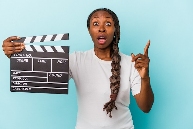 Young african american woman holding clapperboard isolated on blue background having an idea, inspiration concept.
