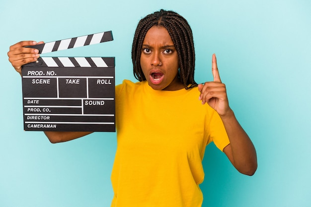 Young african american woman holding a clapperboard isolated on blue background  having an idea, inspiration concept.