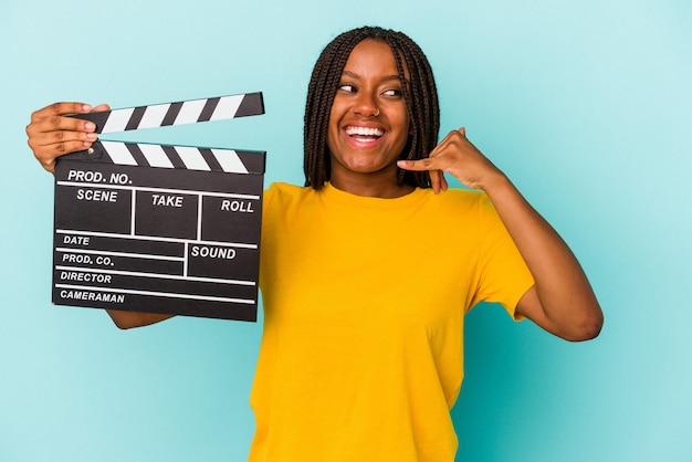 Young african american woman holding a clapperboard isolated on blue background  showing a mobile phone call gesture with fingers.