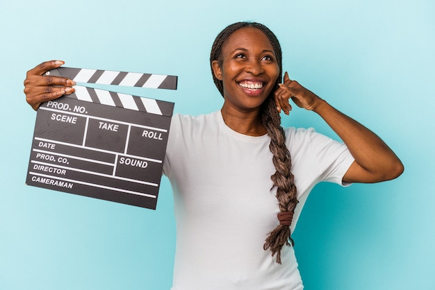 Young african american woman holding clapperboard isolated on blue background showing a mobile phone call gesture with fingers.