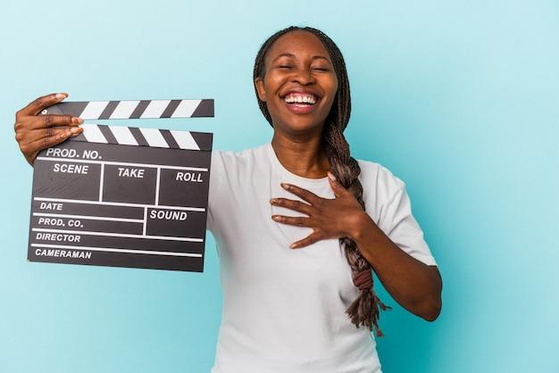 青い背景で隔離のカチンコを保持している若いアフリカ系アメリカ人の女性は、胸に手を置いて大声で笑います。