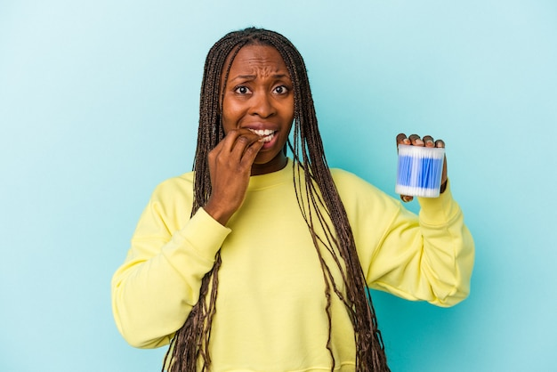 Young african american woman holding cotton bulls isolated on buds background biting fingernails, nervous and very anxious.
