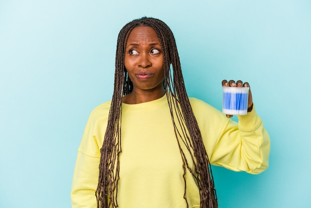 Young african american woman holding cotton bulls isolated on buds background confused, feels doubtful and unsure.
