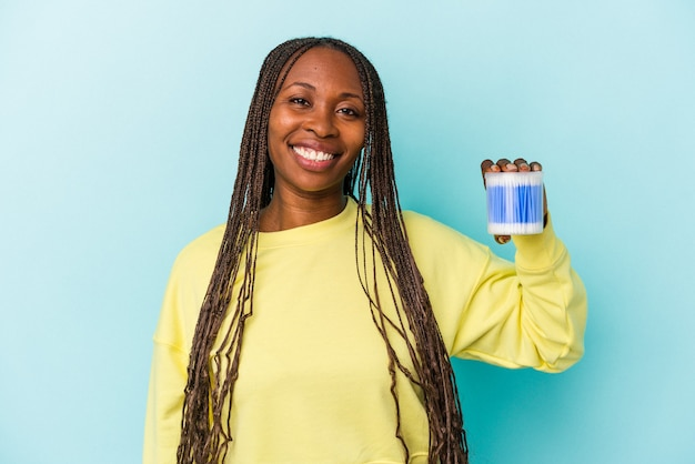 Young african american woman holding cotton bulls isolated on buds background happy, smiling and cheerful.