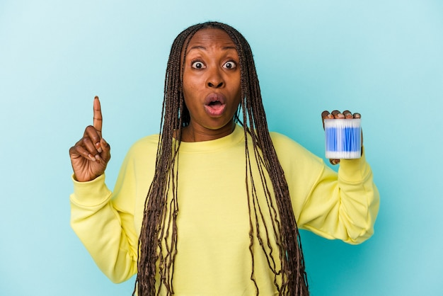 Young african american woman holding cotton bulls isolated on buds background having some great idea, concept of creativity.