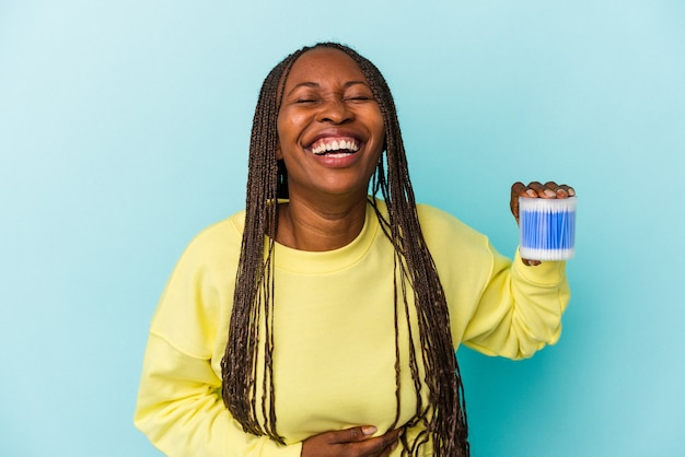 Young african american woman holding cotton bulls isolated on buds background laughing and having fun.