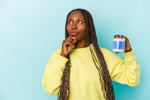 Young african american woman holding cotton bulls isolated on buds background looking sideways with doubtful and skeptical expression.