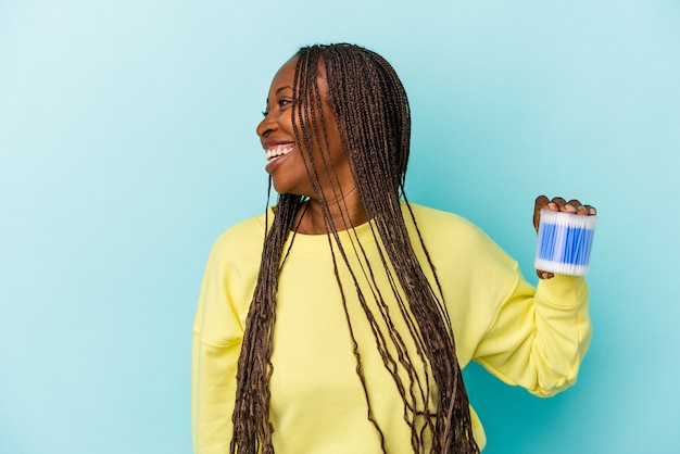 Young african american woman holding cotton bulls isolated on buds background looks aside smiling, cheerful and pleasant.