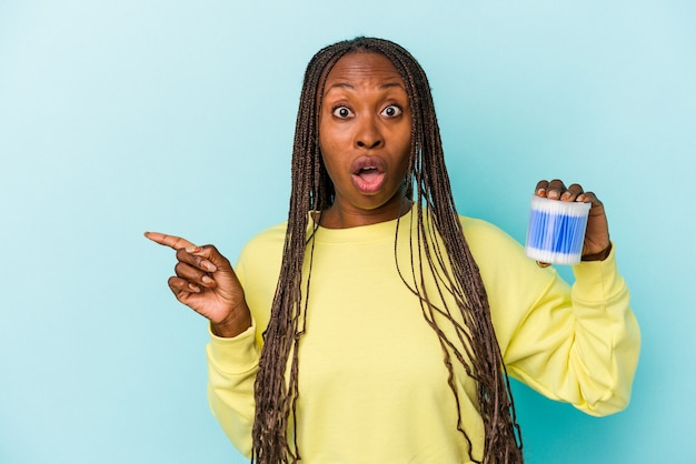 Young african american woman holding cotton bulls isolated on buds background pointing to the side