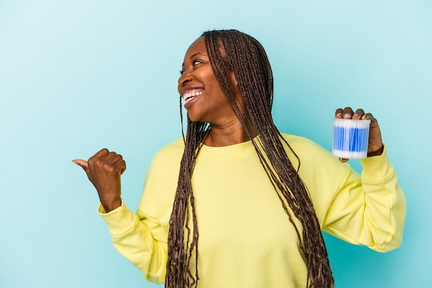Young african american woman holding cotton bulls isolated on buds background points with thumb finger away, laughing and carefree.