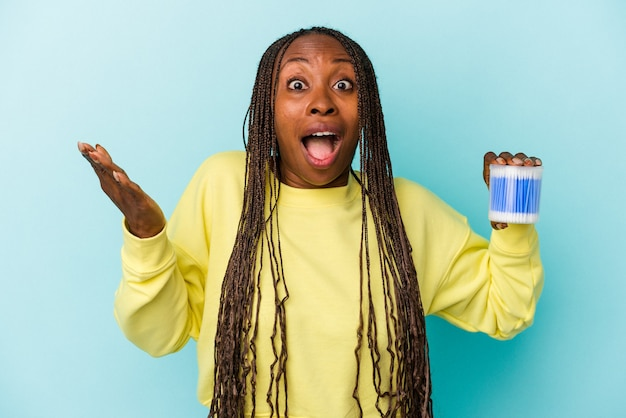 Young african american woman holding cotton bulls isolated on buds background receiving a pleasant surprise, excited and raising hands.