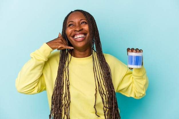 Young african american woman holding cotton bulls isolated on buds background showing a mobile phone call gesture with fingers.