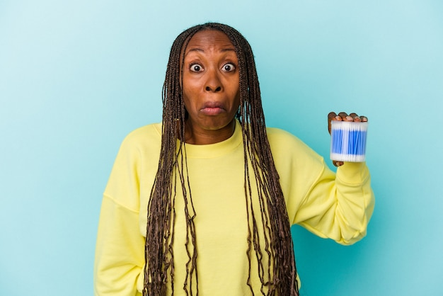 Young african american woman holding cotton bulls isolated on buds background shrugs shoulders and open eyes confused.