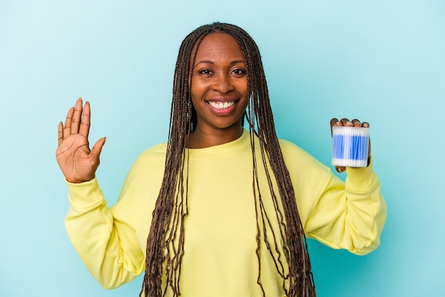 Young african american woman holding cotton bulls isolated on buds background smiling cheerful showing number five with fingers.
