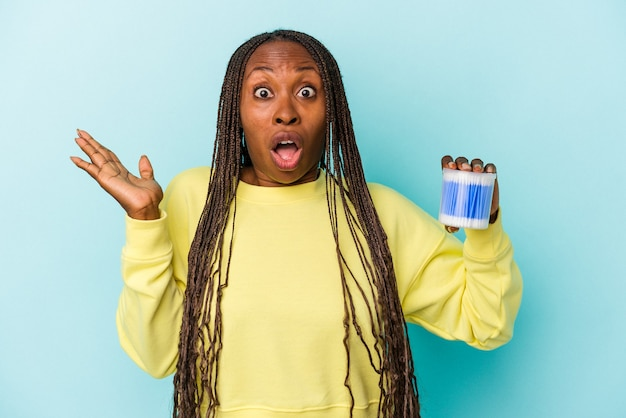 Young african american woman holding cotton bulls isolated on buds background surprised and shocked.