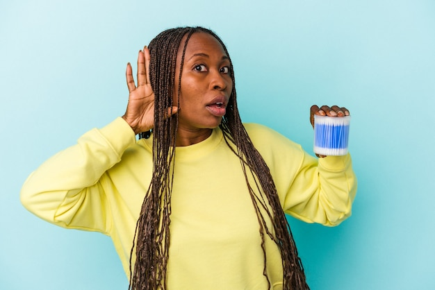 Young african american woman holding cotton bulls isolated on buds background trying to listening a gossip.
