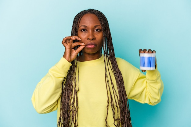 Young african american woman holding cotton bulls isolated on buds background with fingers on lips keeping a secret.