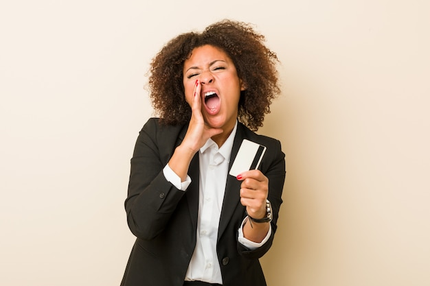 Young african american woman holding a credit card shouting excited to front.