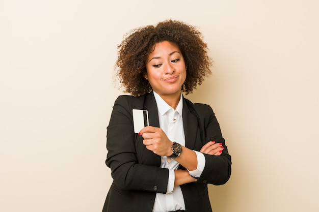 Young african american woman holding a credit card smiling confident with crossed arms.