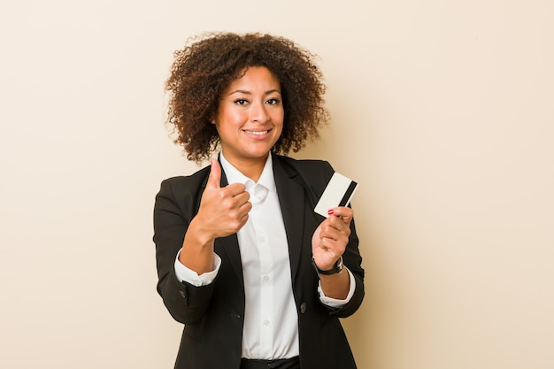 Young african american woman holding a credit card smiling and raising thumb up