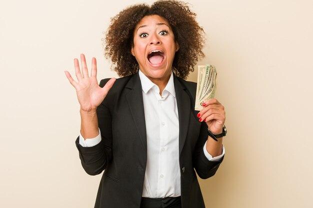 勝利または成功を祝うドルを保持している若いアフリカ系アメリカ人女性
