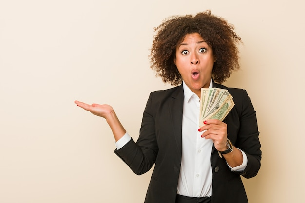 Young african american woman holding dollars impressed holding copy space on palm.
