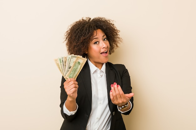 Young african american woman holding dollars pointing with finger you as if inviting come closer.