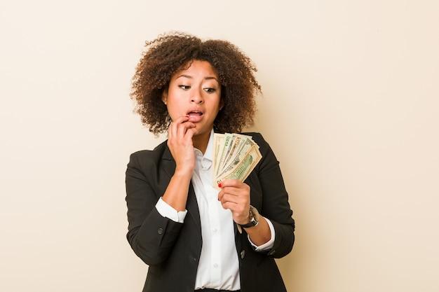 ドルを持っている若いアフリカ系アメリカ人の女性は、コピースペースを見ている何かについて考えてリラックスしました。