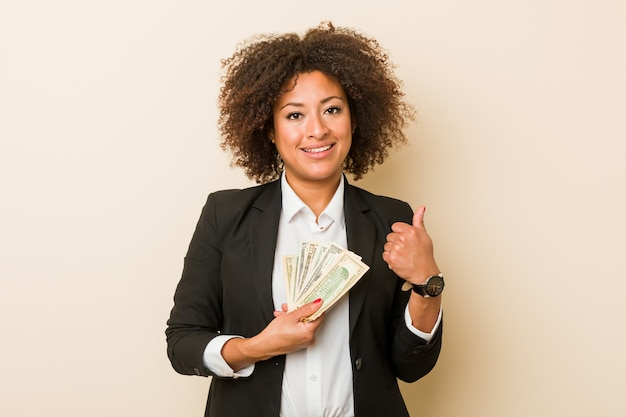 Young african american woman holding dollars smiling and raising thumb up
