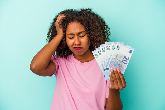 Young african american woman holding euro banknotes isolated on blue background being shocked, she has remembered important meeting.