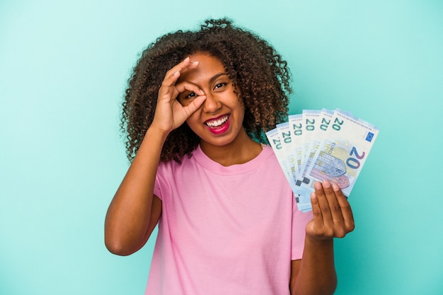 Young african american woman holding euro banknotes isolated on blue background excited keeping ok gesture on eye.
