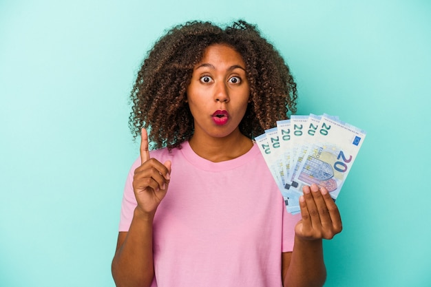 Young african american woman holding euro banknotes isolated on blue background having some great idea, concept of creativity.