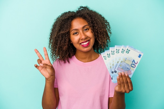 Young african american woman holding euro banknotes isolated on blue background joyful and carefree showing a peace symbol with fingers.