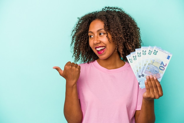 Young african american woman holding euro banknotes isolated on blue background points with thumb finger away, laughing and carefree.