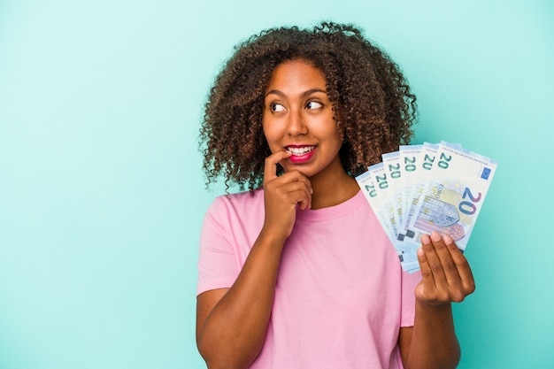 Young african american woman holding euro banknotes isolated on blue background relaxed thinking about something looking at a copy space.