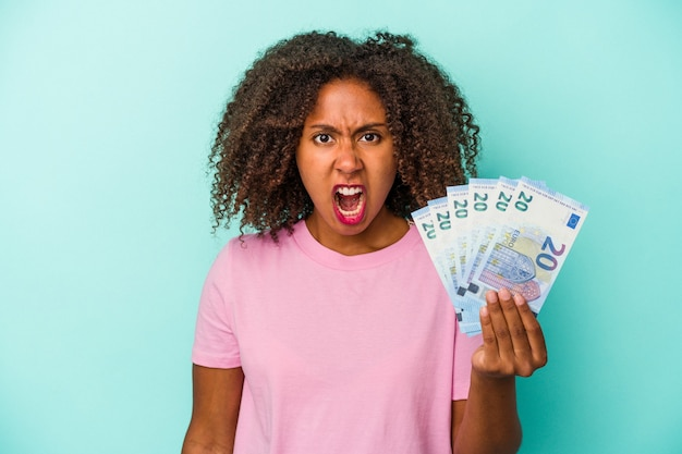 Young african american woman holding euro banknotes isolated on blue background screaming very angry and aggressive.