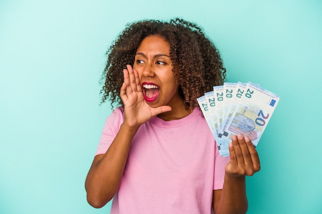 Young african american woman holding euro banknotes isolated on blue background shouting and holding palm near opened mouth.