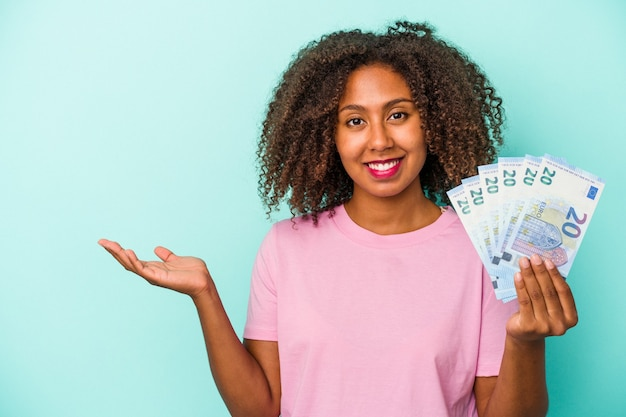 Young african american woman holding euro banknotes isolated on blue background showing a copy space on a palm and holding another hand on waist.